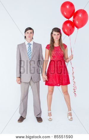 Unsmiling geeky couple standing hand in hand on white background