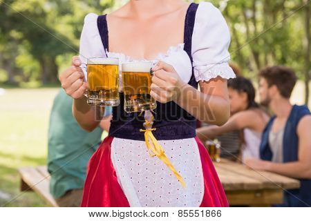 Pretty oktoberfest girl holding beer tankards on a sunny day