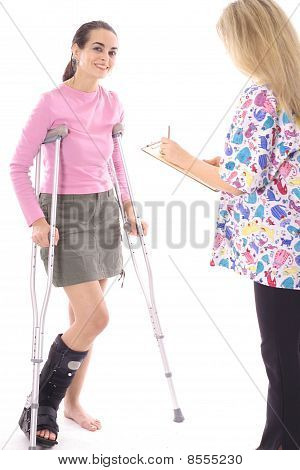 happy woman on crutches talking to nurse