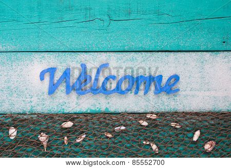 Welcome beach sign with shells and sand