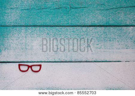 Blank wood beach sign with sand and red sunglasses