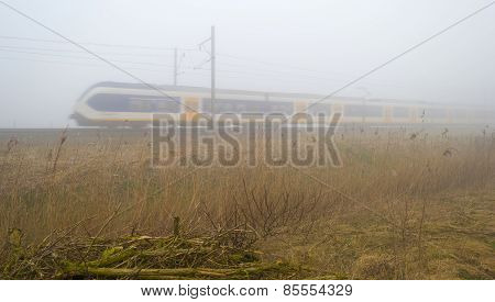 Train moving through a foggy countryside in winter