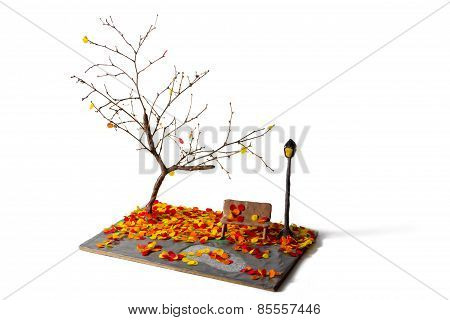 miniature lantern and bench in autumn park made from plasticine sticks and paper