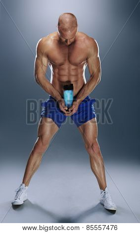 Full Length Portrait of a Shirtless Semi Bald Athletic Man Wearing Blue Gym Shorts Holding Water Bottle While Facing Down on a Gray Gradient Background.