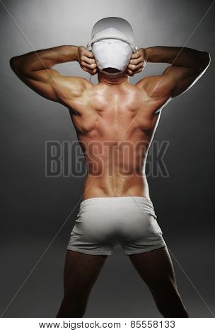 Portrait of a Sexy Topless Athletic Man Showing his Back Muscles with Tattoo on a Gray Background.