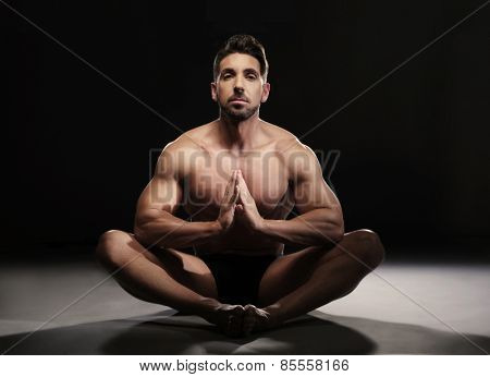 Portrait of a Topless Muscular Man Sitting on the Floor in a Yoga Position Looking at the Camera on a Black Background.