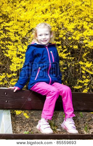 little girl sitting on bench in spring