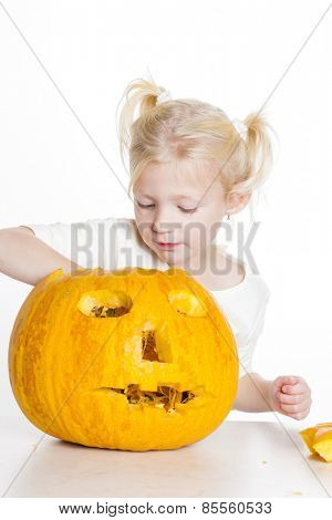 little girl carving pumpkin for Halloween