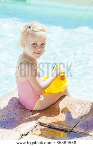 little girl with water sprayer by swimming pool