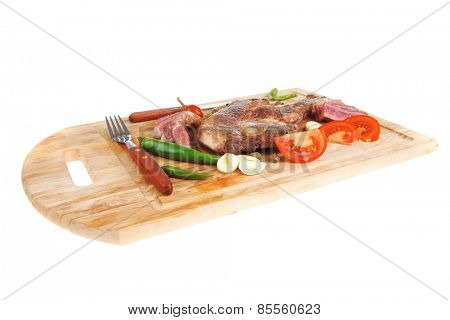fresh grilled beef meat fillet sliced on wooden board with tomatoes and red pepper and cutlery isolated  over white background