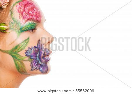 Close up portrait of woman model with hand drawing flowers on her face