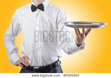 Young waiter with silver tray