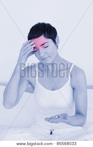 Woman having a headache in her bedroom