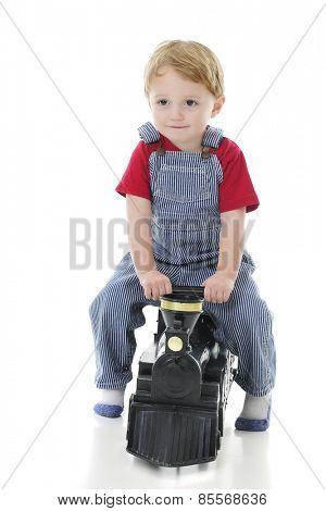 An adorable toddler boy in engineer-style pinstriped overalls scooting along on a black toy train engine.   On a white background.