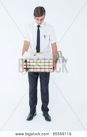 Fired businessman holding box of belongings on white background