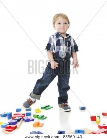 An adorable toddler navigating over a floor strewn with colorful  blocks and stack toys.