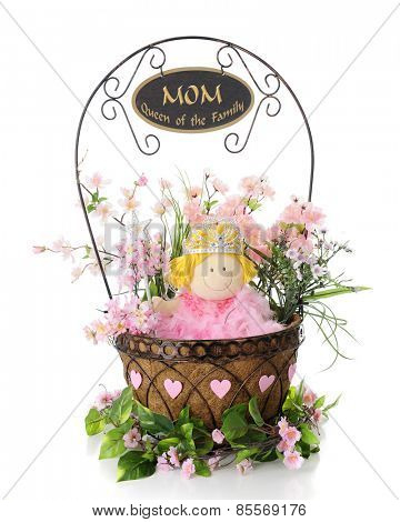A wire basket filled with a doll dressed as a queen among green and pink foliage.  Hearts surround the basket and a sign on the handle reads,