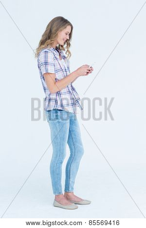 Pretty hipster using her smartphone on white background
