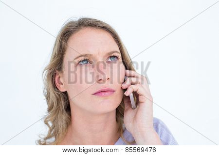 Unsmiling woman calling with her smartphone on white background