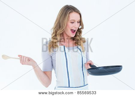 Smiling woman holding frying pan and wooden spoon on white background