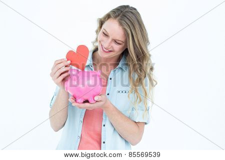 Smiling woman holding piggy bank and red heart on white background