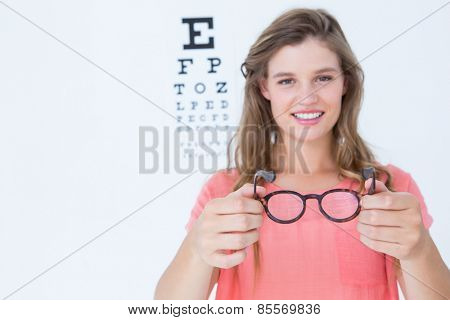 Hipster showing glasses next to an eye test on white background