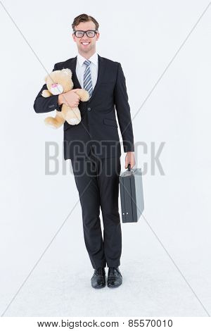 Geeky hipster businessman holding briefcase and teddy on white background