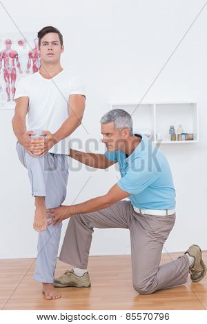 Doctor examining his patient legs in medical office