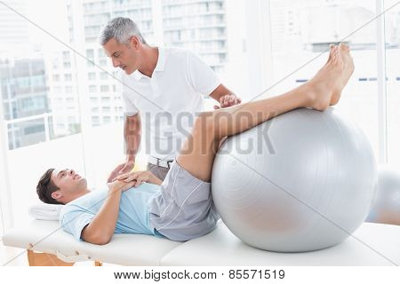 Therapist helping his patient with exercise ball in medical office