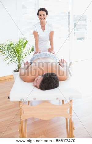 Patient relaxing on the massage table with physiotherapist behind in medical office