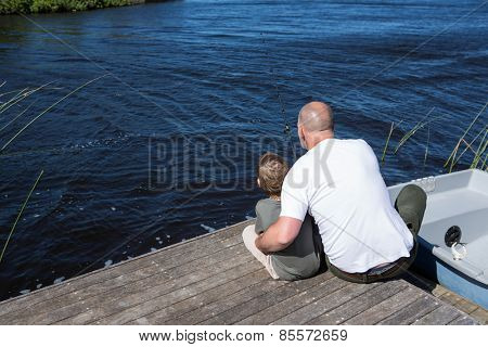 Happy man sitting with his son in the countryside