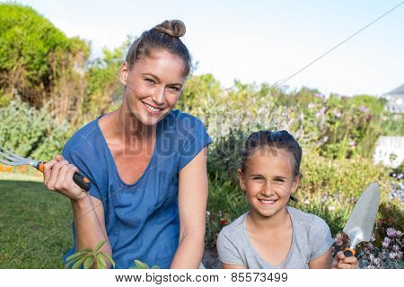 Mother and daughter tending to flowers in the garden