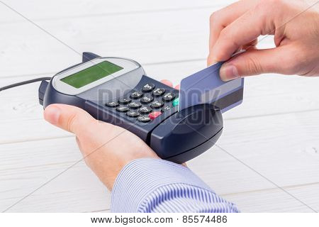 Man swiping his credit card on a wooden table