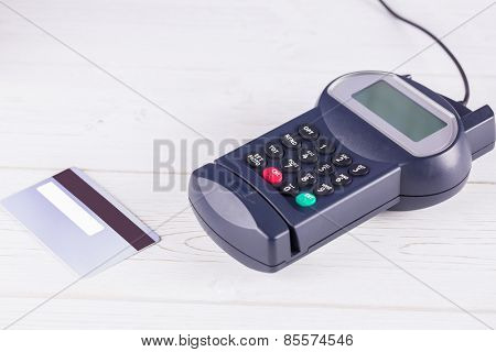Pin terminal and credit card on a wooden table