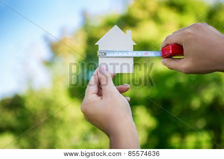 Man's hand measures the cardboard house