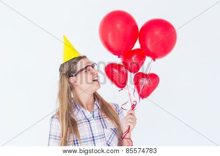Geeky hipster holding red balloons on white background