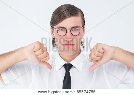 Geeky businessman looking at camera thumbs down on white background
