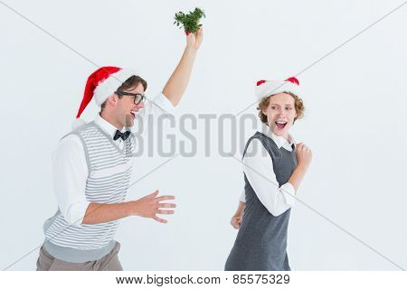Geeky hipster running away from a man with mistletoe on white background