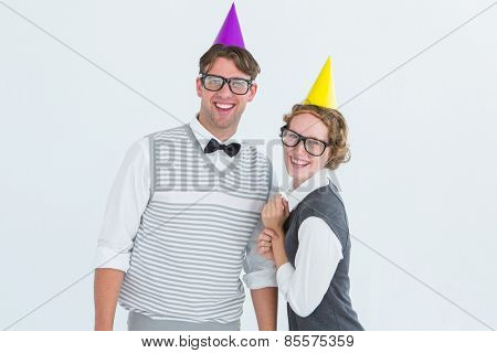 Happy geeky hipster couple with party hat on white background