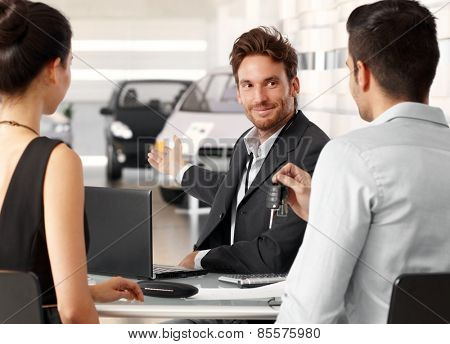Successful dealer selling car in showroom to young couple. All sitting at desk, man holding keys.