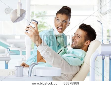 Male patient making selfie of dental check-up.