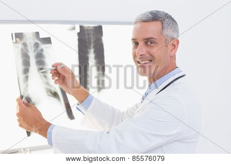 Smiling doctor looking at X-Rays in medical office