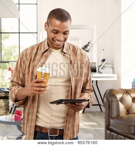 Happy young black man using tablet at home, drinking coffee.