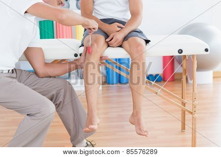 Doctor checking reflexes of the knee of his patient