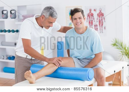 Doctor examining his patient leg in medical office