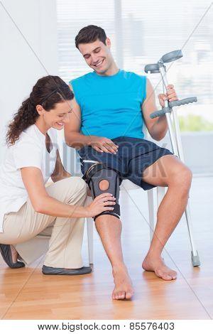Doctor examining her patient knee in medical office