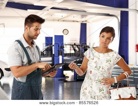Elegant young woman with disgust on face handing car key to car mechanic.