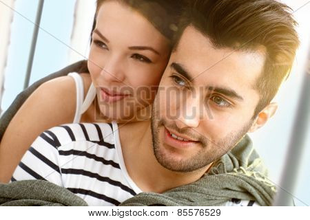 Closeup portrait of attractive young loving couple embracing on sailing boat.