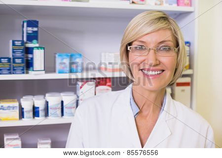 Smiling pharmacist in lab coat looking at camera in the pharmacy