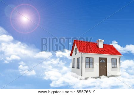 White house with red gable roof and chimney in clouds. Background sun shines brightly
